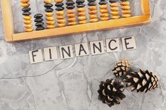 Word FINANCE laid out of handwritten letters on cardboard squares near old wooden abacus and three cones. On gray cracked concrete stock images