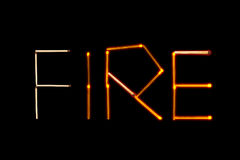 The word `fire`, laid out with matches. On black background Stock Images