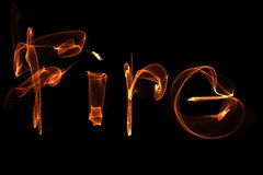Word fire wave motion glowing lines on dark background. Word fire of waves of glowing lines in different shapes and colors Royalty Free Stock Image
