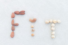 Word Fit made of different nuts on the light background royalty free stock photos