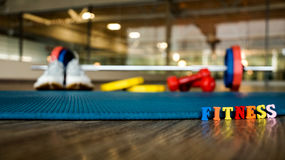 The word `Fitness` is built of colorful wooden letters with blurred back-up dumbbell, running shoes, weights and Mat. Photo Stock Photography