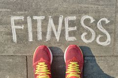 Free Word Fitness Written On Gray Pavement With Woman Legs In Sneakers, View From Above Stock Images - 144227284