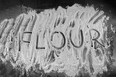 Word flour written in flour on table Stock Image