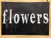 The word flowers written on a blackboard with wooden frame Stock Images