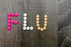 The word flu written with pills on a wooden background. Stock Image