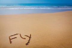 Word Fly Written in Sand on Tropical Beach Stock Photography