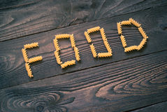 Word FOOD written pasta on the wooden table Stock Images