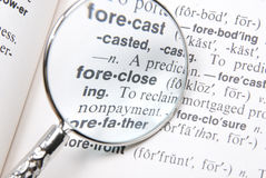 Word 'Foreclose' magnified. Magnifying glass held over Foreclose entry in dictionary Royalty Free Stock Photos