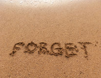 Word Forget on sand. Word Forget in handwriting on sandy beach Stock Photography