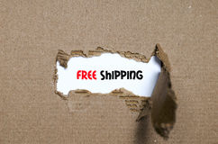 The word free shipping appearing behind torn paper. The word free shipping behind torn paper Stock Photography
