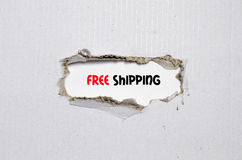The word free shipping appearing behind torn paper. The word free shipping behind torn paper Stock Images