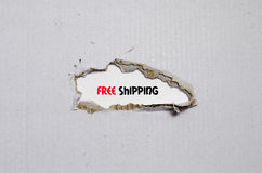 The word free shipping appearing behind torn paper. The word free shipping behind torn paper Royalty Free Stock Photo