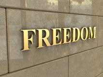 Word Freedom. The word Freedom is chiseled by gold letters on a stone wall Stock Photos