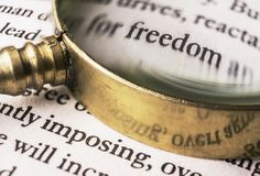 The word freedom read through a magnifying glass. An evocative image of the word `freedom` emphasized with an old and golden magnifying glass. It could symbolize Stock Photos