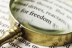 The word freedom read through a magnifying glass. An evocative image of the word `freedom` emphasized with an old and golden magnifying glass. It could symbolize Stock Images
