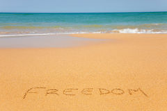 The word Freedom written on the beach sand. With wave approaching Royalty Free Stock Image