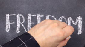 Word FREEDOM, written by hand in chalk on a blackboard. Hand encircles the words on the board stock footage