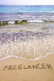 Word FREELANCER written in sand, on a beautiful beach Stock Photography