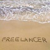 Word FREELANCER in zand, op een mooi strand wordt geschreven dat Stock Foto's