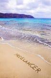 Word FREELANCER in zand, op een mooi strand wordt geschreven dat stock afbeeldingen