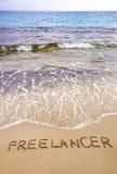 Word FREELANCER in zand, op een mooi strand wordt geschreven dat Stock Fotografie