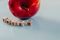 The word fresh written in cubes and an apple. The word fresh written in cubes and a red apple royalty free stock photography