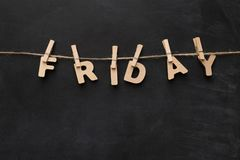 Friday word made of wooden letters. Word Friday spelled with wooden letters on black background. Characters handing on clothespins, top view, copy space Royalty Free Stock Image