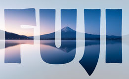 Word FUJI transparent over mountain Fuji at dawn with peaceful lake reflection.  royalty free stock photos