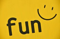 Word FUN and smile icon painted on yellow. Word FUN and smile icon painted black on vivid yellow background, close up Stock Image