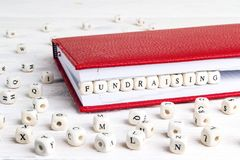Word Fundraising written in wooden blocks in red notebook on white wooden table. stock photos