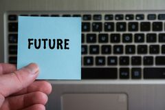 Word FUTURE on sticky note. Hold in hand on laptop keyboard background stock photography