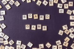 Word GAME With Wooden Letters On Black Board With Dice And Letter In The Circle Stock Photo