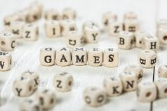 Games word written on wood block. Word GAMES formed by wood alphabet blocks. On old wooden table Stock Image
