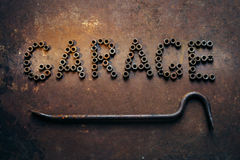 The word Garage is written by old screw  nuts. Nearby the  crowb Stock Photography