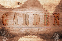 Word garden written, burned letters on wooden brown background. Royalty Free Stock Photo