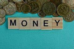 Word geld van houten brieven op een groene achtergrond met kleine muntstukken royalty-vrije stock afbeelding