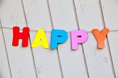 Word gelukkig door gekleurde brieven op omheining Stock Foto's