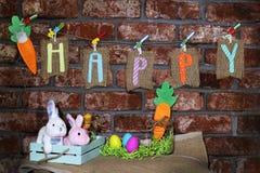 Word Gelukkig op jute etiketteert het hangen op een lijn met oranje wortel, kleurrijke paaseieren, glaskruik en Pasen-konijntjesk Royalty-vrije Stock Foto