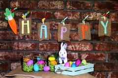 Word Gelukkig op jute etiketteert het hangen op een lijn met oranje wortel, kleurrijke paaseieren in glaskruiken en wit konijntje Stock Foto