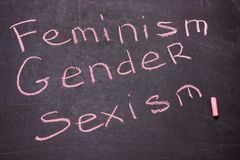 The word gender, feminism, sexism is written chalk. On the blackboard.The concept of equality royalty free stock image