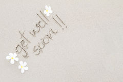 The word get well soon with white flowers on the beach surface b Stock Image