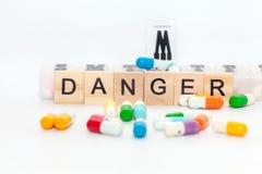 Word gevaar met kleurrijke pil op wit stock fotografie