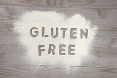 Word gluten free written in white flour. On a old wooden table, vintage tone Royalty Free Stock Photos