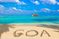 Word Goa on beach. Concept holiday background stock photography