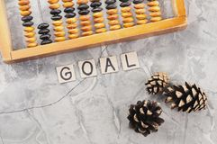 Word GOAL laid out of handwritten letters on cardboard squares near old wooden abacus and three cones. On gray cracked concrete royalty free stock images