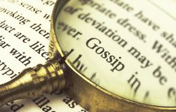 The word `gossip` emphasized by a magnifying glass. The word `gossip` emphasized by a magnifying glass and wrapped with blurry text Stock Photos