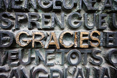 Word GRACIES in gold in center of bronze plaque Stock Photo