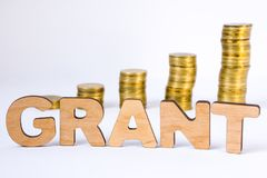 Word grant of three-dimensional letters is in foreground with growth columns of coins on blurred background. Monetary grant concep. T for starting or development royalty free stock images