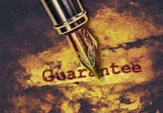 Word Guarantee and a pen. Word Guarantee and a fountain pen on dark golden background Royalty Free Stock Photos