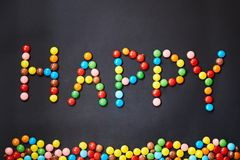 The word happiness is made of colored candies.  English alphabet. Happy. The word happiness is made of colored candies. On black background. English alphabet Royalty Free Stock Photography